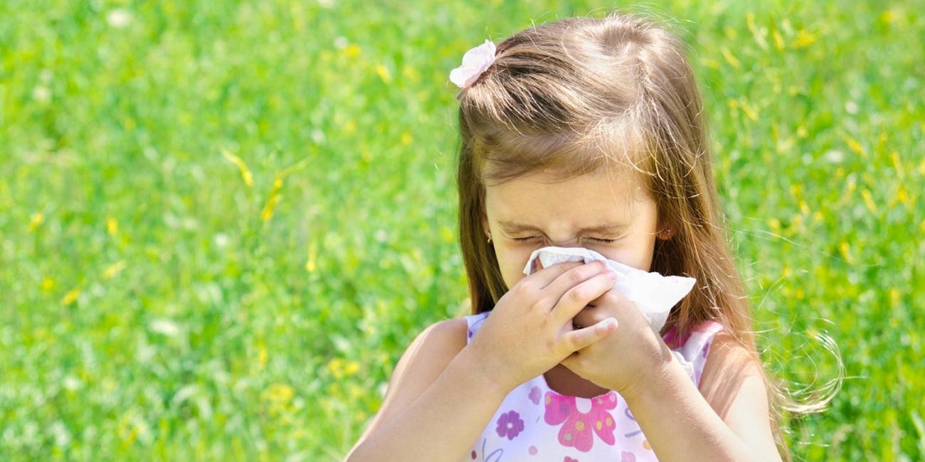 girl sneezing outside
